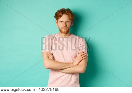 Gloomy Redhead Guy Feeling Offended, Frowning Upser With Arms Crossed On Chest, Looking Insulted And