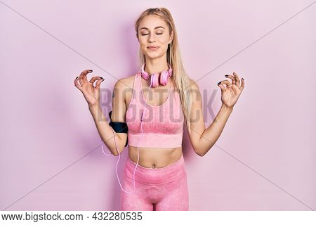 Young beautiful caucasian woman wearing gym clothes and using headphones relax and smiling with eyes closed doing meditation gesture with fingers. yoga concept.
