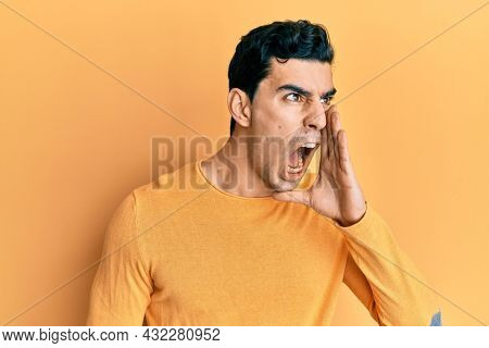 Handsome hispanic man wearing casual clothes shouting and screaming loud to side with hand on mouth. communication concept.