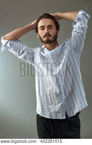 Men's beauty and hairstyle. Handsome brunet man posing at studio in light shirt and trousers. Men's fashion.