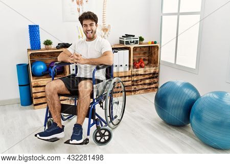 Hispanic man sitting on wheelchair at physiotherapy clinic sticking tongue out happy with funny expression. emotion concept.