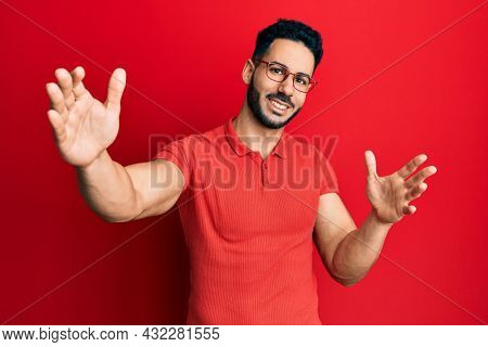 Young hispanic man wearing casual clothes and glasses looking at the camera smiling with open arms for hug. cheerful expression embracing happiness.