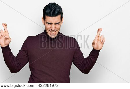 Handsome hispanic man wearing casual turtleneck sweater gesturing finger crossed smiling with hope and eyes closed. luck and superstitious concept.