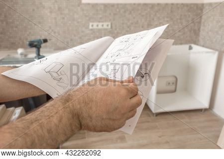 Kitchen Installation. Man Holds Instructions For Installing Kitchen Furniture In His Hands