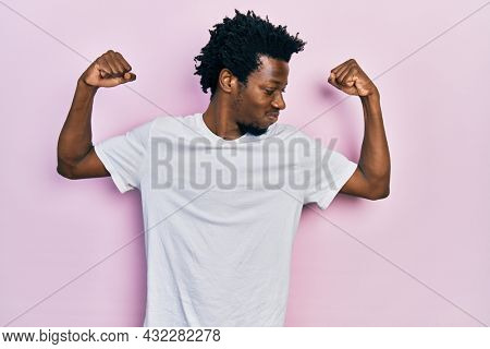 Young african american man wearing casual white t shirt showing arms muscles smiling proud. fitness concept.