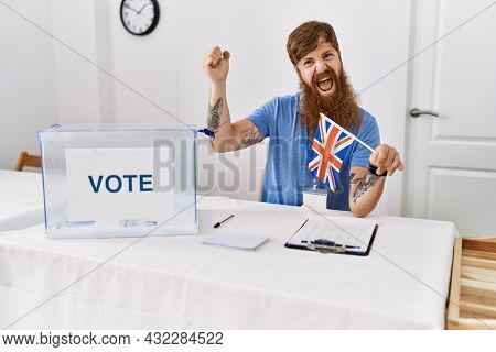 Caucasian man with long beard at political campaign election holding uk flag screaming proud, celebrating victory and success very excited with raised arms