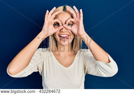 Beautiful blonde woman wearing casual sweater doing ok gesture like binoculars sticking tongue out, eyes looking through fingers. crazy expression.