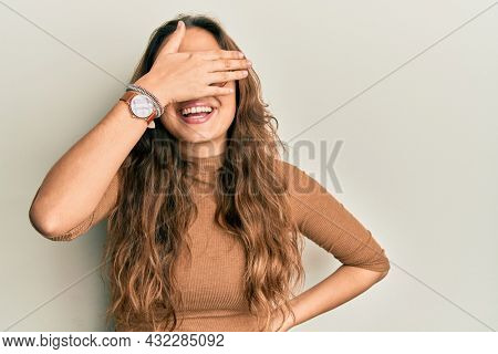 Young hispanic girl wearing casual clothes and glasses smiling and laughing with hand on face covering eyes for surprise. blind concept.