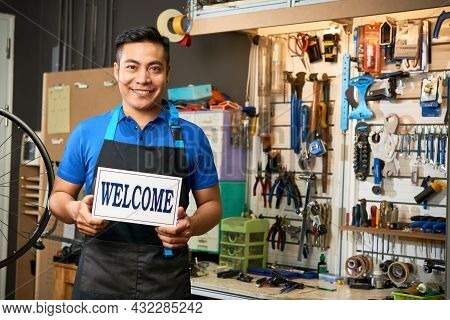 Portrait Og Happy Smiling Bicycle Mechanic Opening Workshop And Showing Signboard