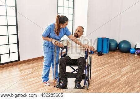 Senior man sitting on wheelchair being assited by geriatric nurse