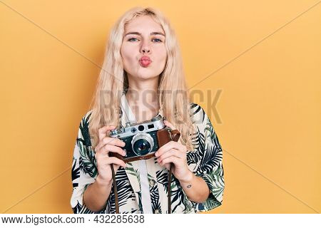 Beautiful caucasian woman with blond hair holding vintage camera looking at the camera blowing a kiss being lovely and sexy. love expression.