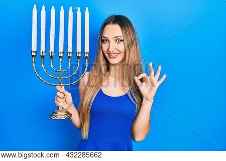 Young blonde girl holding menorah hanukkah jewish candle doing ok sign with fingers, smiling friendly gesturing excellent symbol