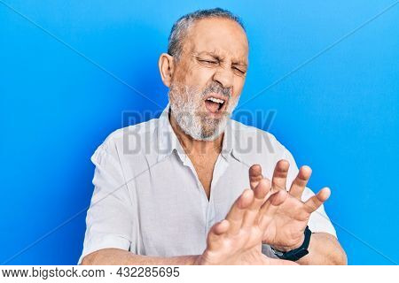 Handsome senior man with beard wearing casual white shirt disgusted expression, displeased and fearful doing disgust face because aversion reaction. with hands raised