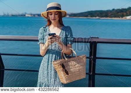 Young Beautiful Female Staying On The Pier And Surfing Smartphone On Sunny Day. Wearing Fashionable