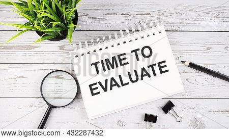 Time To Evaluate Text Concept Write On Notebook With Office Tools On The Wooden Background