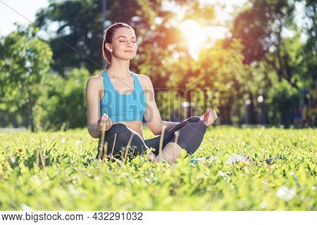 Girl Meditates In Lotus Pose On Green Grass. Portrait Of Caucasian Young Woman With Closed Eyes. Tra
