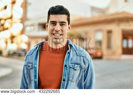 Young hispanic man smiling happy standing at the city.