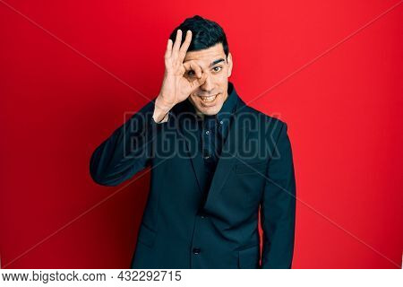 Handsome hispanic man wearing business clothes doing ok gesture with hand smiling, eye looking through fingers with happy face.