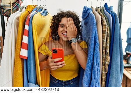 Young hispanic woman searching clothes on clothing rack using smartphone covering one eye with hand, confident smile on face and surprise emotion.