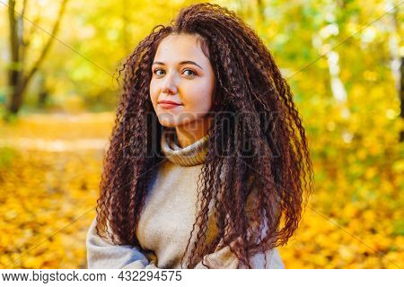 Beautiful Afro-haired Woman Wearing Warm Sweater Walk In Autumn Park At Sunny Warm Day. Portrait Of
