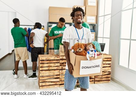 Group of young african american volunteers working at charity center. Man smiling happy and holding box with toys to donate.