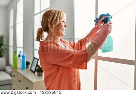 Middle age woman smiling happy cleaning using diffuser and rag at home.