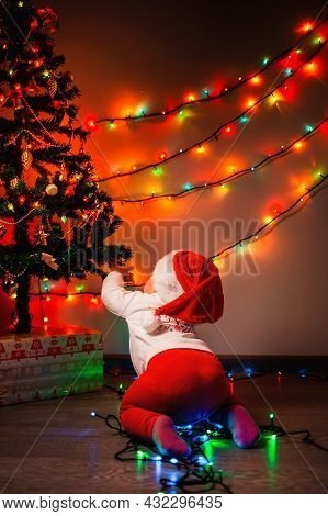 Christmas. A Cute Baby In A Christmas Hat Crawls Around A Christmas Tree Decorated With Glowing Ligh