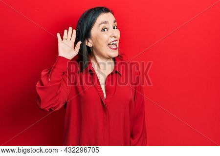 Middle age hispanic woman wearing casual clothes waiving saying hello happy and smiling, friendly welcome gesture