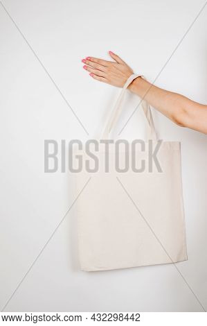 Female Hand Holding Eco-bag. Mocap Of Reusable Cotton Eco-bag On White Insulated Background, Concept