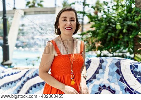 Middle age hispanic woman smiling happy and confident outdoors at the city