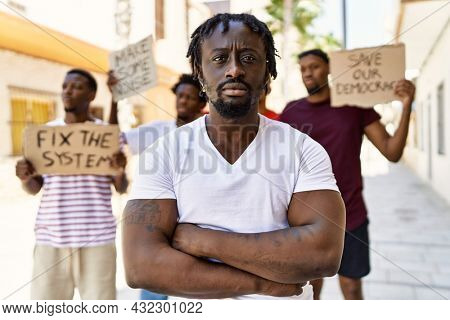 Young activist man with arms crossed gesture standing with a group of protesters holding banner protesting at the city.