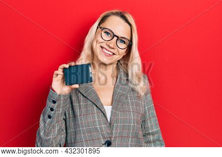 Beautiful caucasian blonde business woman holding ssd memory looking positive and happy standing and smiling with a confident smile showing teeth