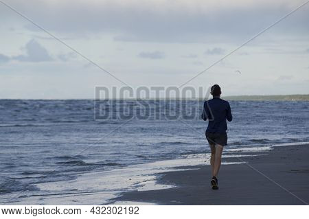 Exercising Outside. A Jogger In Lightweight Blue Long Sleeve T-shirt, Shorts And Running Sneakers Tr