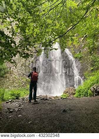 Back view on a man hiker looking Queureuilh waterfall, Le Mont-Dore, Puy-de-Dome, Auvergne, France