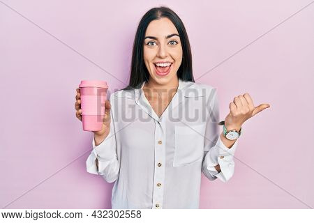 Beautiful woman with blue eyes drinking a take away cup of coffee pointing thumb up to the side smiling happy with open mouth