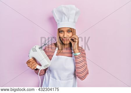 Beautiful hispanic woman holding pastry blender electric mixer mouth and lips shut as zip with fingers. secret and silent, taboo talking