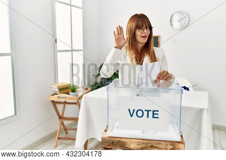 Hispanic business woman voting putting envelop in ballot box waiving saying hello happy and smiling, friendly welcome gesture