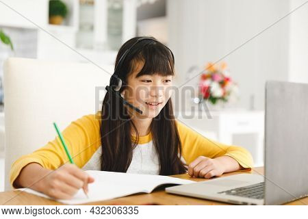Asian girl sitting at table and using laptop during online lessons. childhood, education and discovery using technology at home.