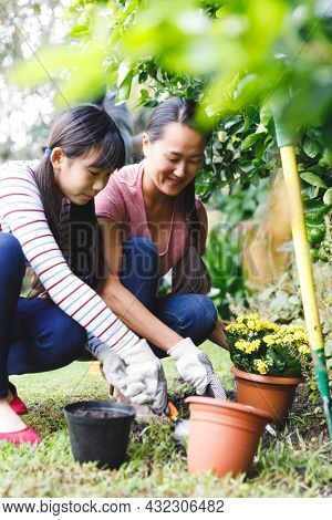 Happy asian mother and daughter smiling, wearing gloves and working in garden. family leisure time at home gardening.