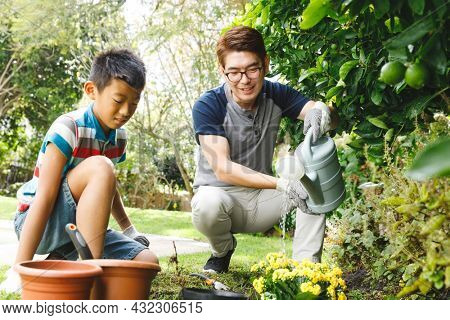 Happy asian father and son smiling, wearing gloves and watering plants together in garden. family leisure time at home gardening.