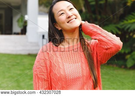 Portrait of happy asian woman smiling in garden outside family home wearing pink sweater. enjoying leisure time alone at home.
