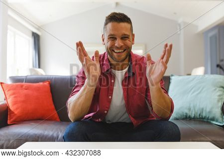 Happy caucasian man sitting on couch having video call in living room, smiling and gesturing. keeping in touch, leisure time at home with communication technology.