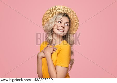 Happy Dreamy Young Blond Haired Female In Yellow T Shirt And Straw Hat Keeping Hands On Chest And Lo