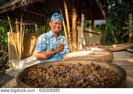 Bali - Indonesia 10.21.2015 - Balinese Indonesian Man In Traditional Cloths Smiling And Checking Luw