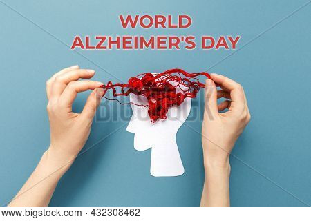 World Alzheimer's Day. Female's Hands Unravel The Tangled Red Threads On The Silhouette Of The Head,