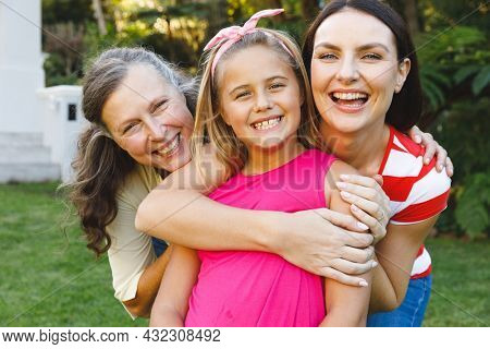 Portrait of smiling caucasian grandmother with adult daughter and granddaughter in garden. multi generation family enjoying leisure time together at home.