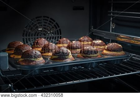 Baking process of chocolate muffins in oven, home made. Sweet cupcakes with cocoa baked in oven.