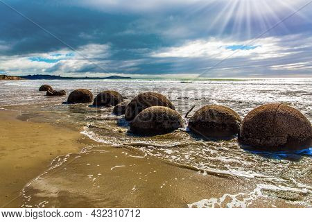 Moeraki boulders. Group of large round boulders on the coast of New Zealand. Sunset. The sun's rays are reflected in the ocean water. Low tide in the Pacific ocean.