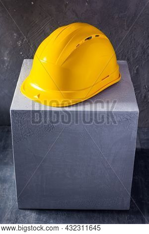 Helmet or hardhat at concrete cube or cement block background texture. Construction concept