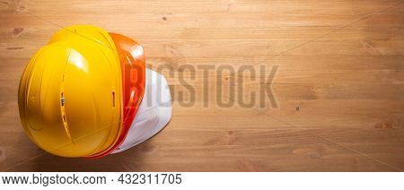 Construction helmet at wood table background texture. Hardhat on wooden floor or wall